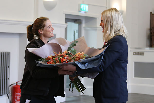 Helen Richardson Walsh receives flowers from Captain of the Hockey team